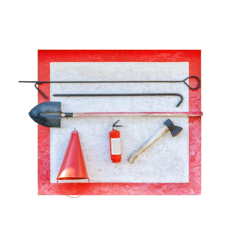 Wall-mounted fire shield with fire-fighting tools. Shovel, hook , axe, cone bucket, fire extinguisher and other. Equipment hanged on fire point.Isolated on royalty free stock photography