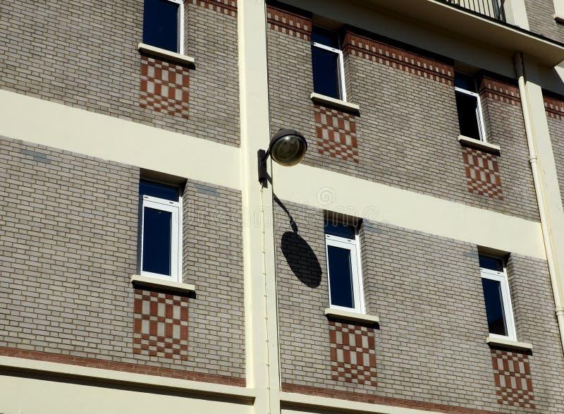Wall-mounted outdoor lamp and its shadow. Wall-mounted outdoor lamp with shadow projected on grey-brick wall, horizontal format royalty free stock images