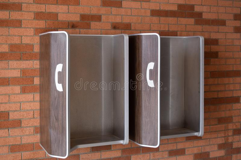 Wall mounted pay phone stations. Old style pay phone stations mounted on a brick wall stock images