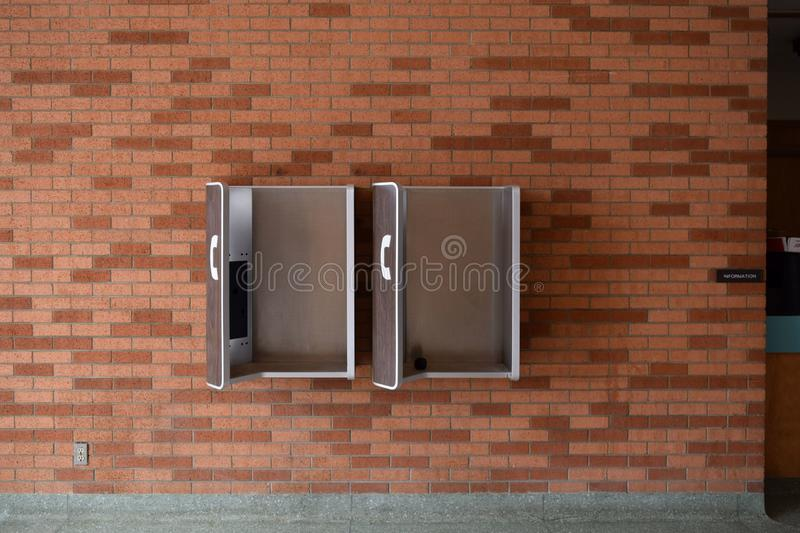Wall mounted pay phone stations. Old style pay phone stations mounted on a brick wall stock photography