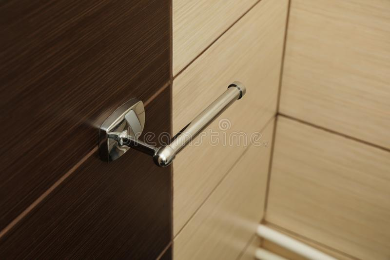 Wall mounted toilet paper holder. In bathroom royalty free stock photos