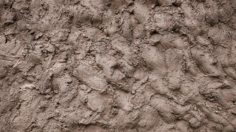 A wall of mud, cement putty decorative background, a mixture of earth smeared on the ground, a pattern of clay on the stock photo