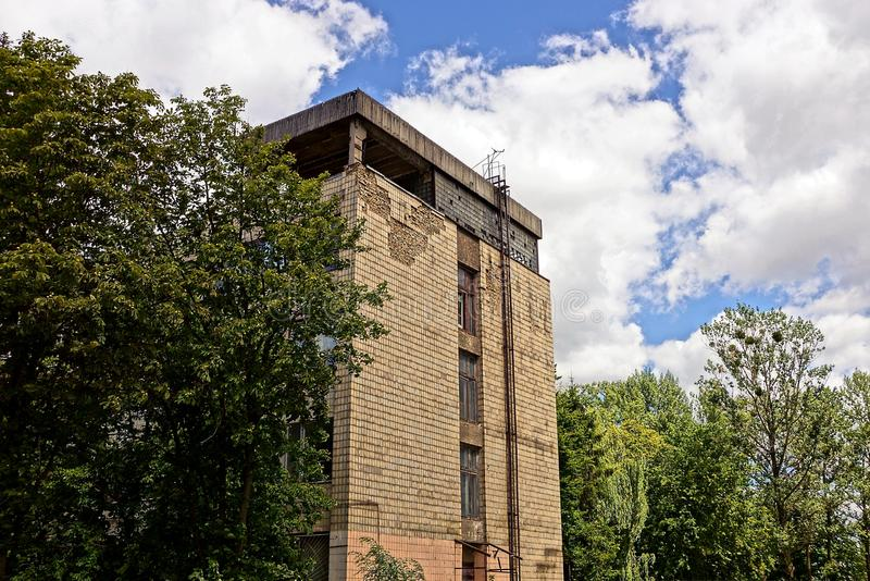 The wall of an old brown house in the branches of trees against the sky and clouds. High old industrial building in green trees against the sky stock photo