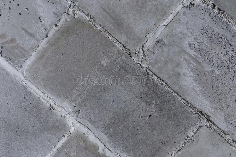 The wall of the old town walls of concrete, gray, porous blocks diagonal fragment. The wall of the old city, built of concrete, gray, porous, shabby blocks royalty free stock images