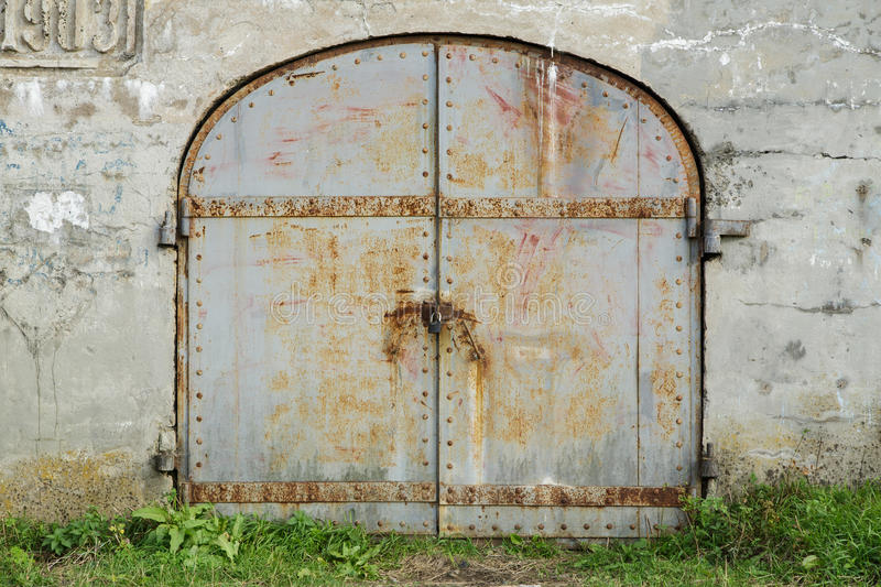 Wall with old iron doors on the lock. Vladivostok, Russia - October 01th, 2016: Vladivostok, the Fortress Pospelovs Fort, an old wall with old iron doors on the royalty free stock photography