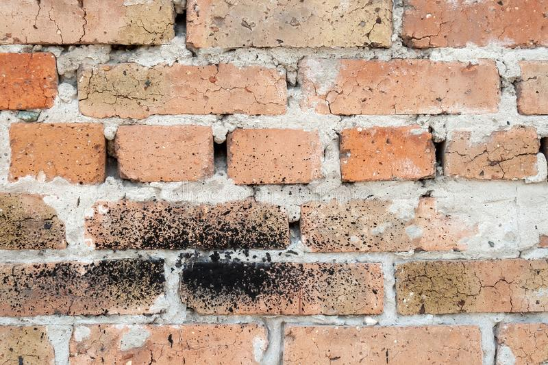 Wall of old orange red cracked brick with a thick layer of cement between them. Some bricks have a black spot royalty free stock photography