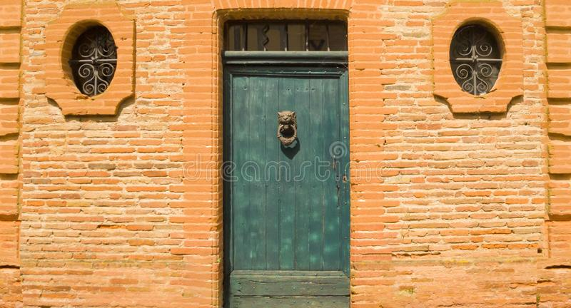The wall of an old red brick house with a blue wooden door and windows stock photos