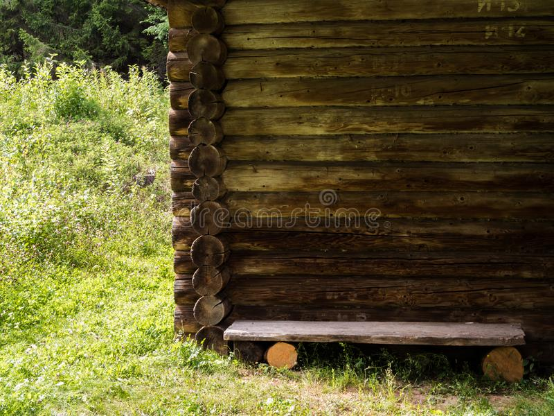 Wall of old rustic log house and wooden bench in the middle of a green meadow. Elements of an old rustic house made of wooden logs royalty free stock images