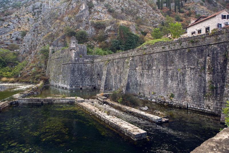 Wall of an old stone fortress by the water stock photography