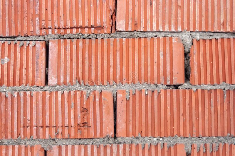 Wall of orange striped bricks with a thick layer of cement between them royalty free stock photos