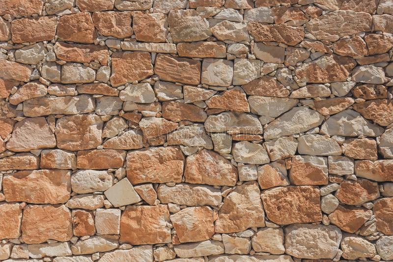 The wall of oval cobblestone color red and orange color, background texture royalty free stock images