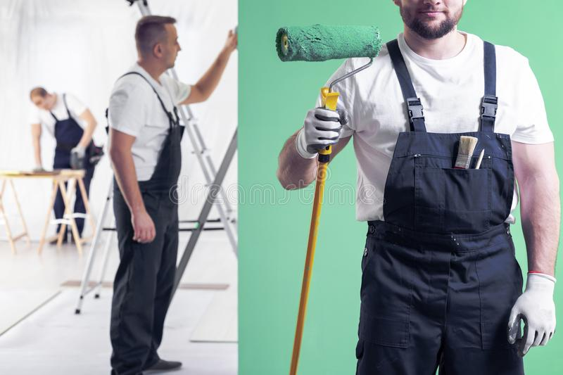 Wall painter in dungarees holding a paint roller on a neo mint g. Reen wall background and home interior renovation crew in the background royalty free stock photo