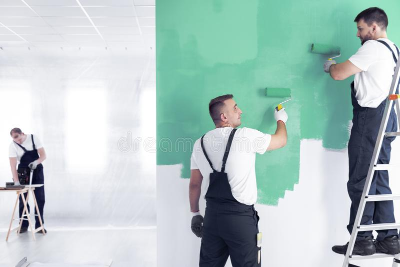 Wall painter on a ladder and a renovation crew worker painting a. Wall green with rollers and a carpenter in a blurry background in a spacious office interior stock photography
