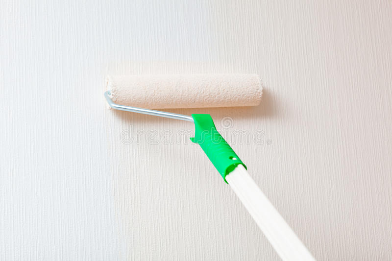 Wall painting with paint roller stock photography