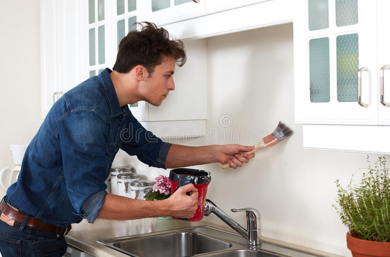 Wall painting. Professional painter man with brush painting kitchen wall. Renovation royalty free stock images
