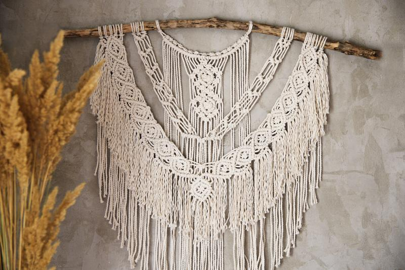 Large Macrame Wall Hanging. Wall panel in the style of Boho made of cotton threads in natural color using the macrame technique for home decor and wedding royalty free stock image
