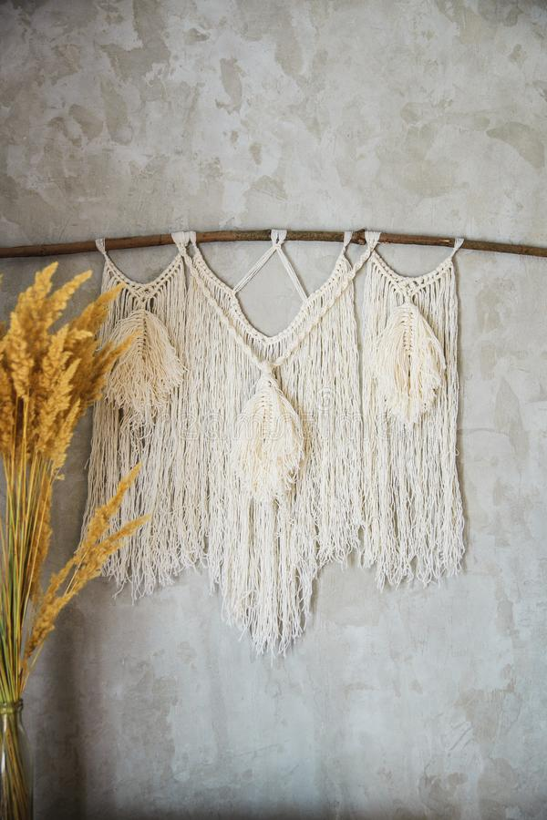 Macrame Wall Hanging. Wall panel in the style of Boho made of cotton threads in natural color using the macrame technique for home decor and wedding decoration royalty free stock images