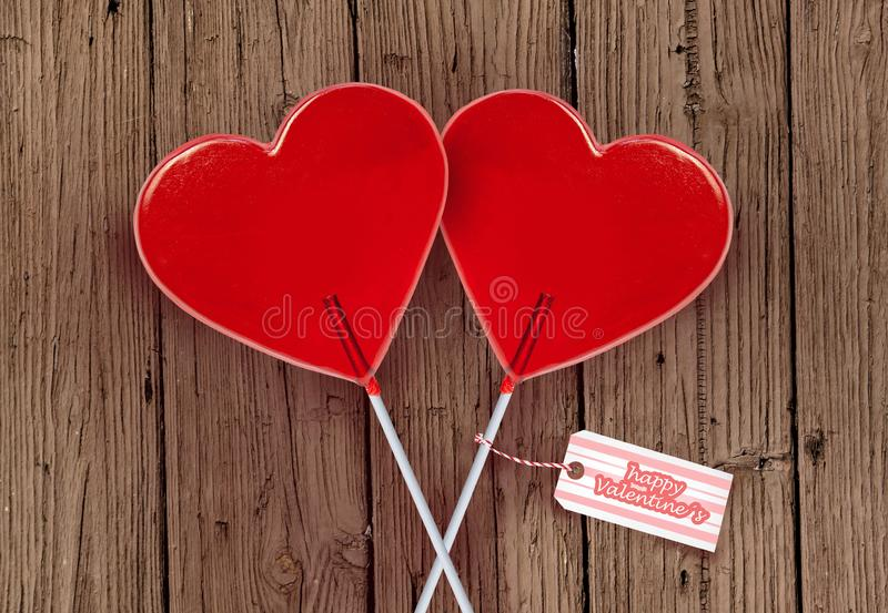 Wall paper Valentines day greeting card with couple of red heart shape lollipops together isolated on vintage wooden table stock image