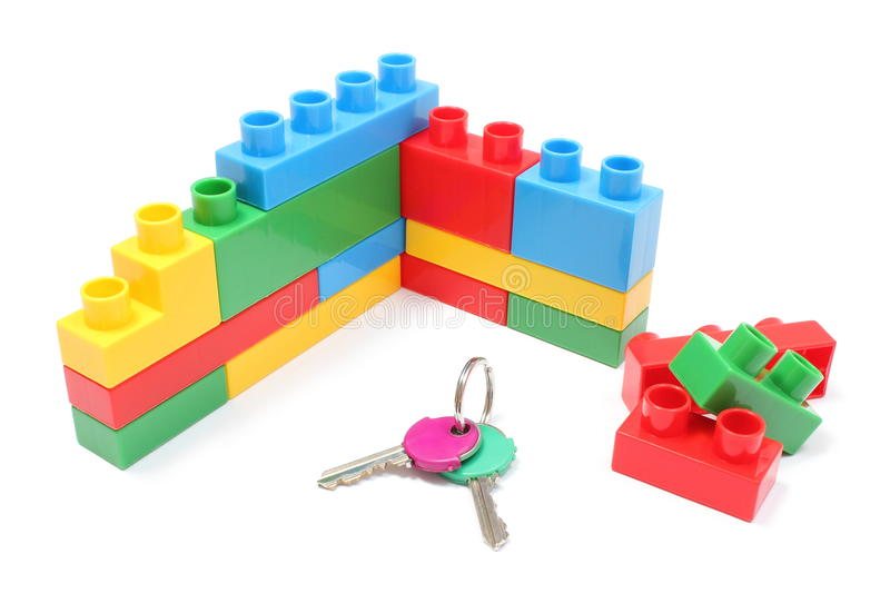 Wall of plastic colorful building blocks with home keys on white background. Closeup of home keys and wall of plastic colorful building blocks, building blocks stock images