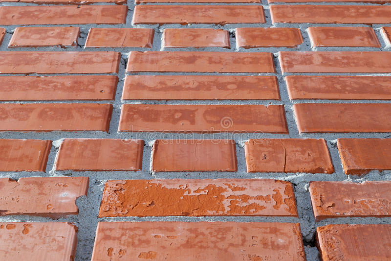 Wall of red brick. Some of the bricks with spots, visiblename and cracks. royalty free stock images