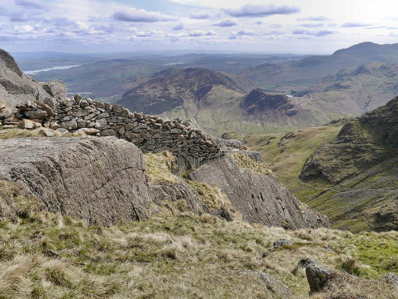Wall remains by Pavey Ark, Lake District. Close to Pavey ark an unexpected wall with Great Langdale below and the relatively small Side Pike right of centre stock photos