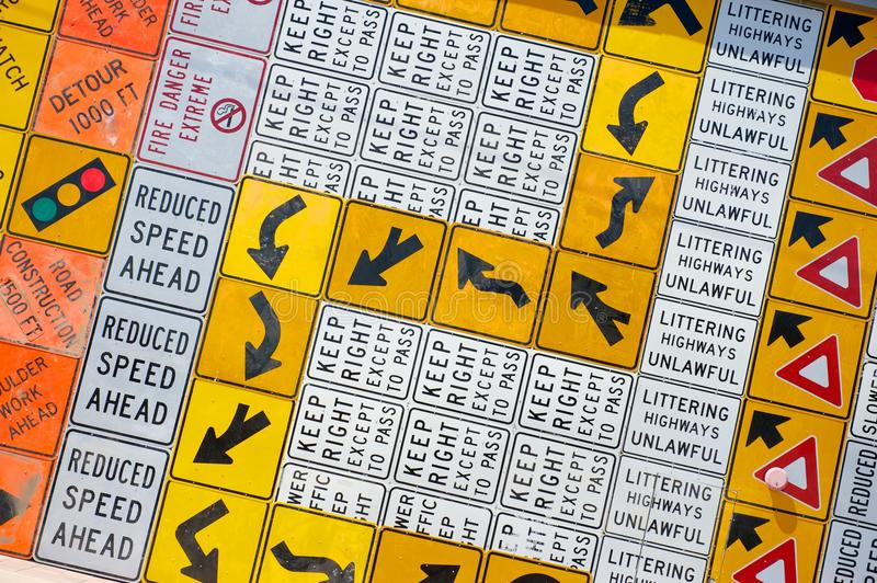 Wall of Road Warning Signs. A wall completely covered in old and worn road or street warning signs stock photos