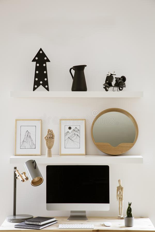 Wall shelves with decor and simple posters above wooden home office desk with metal lamp, mockup monitor and notebooks in white in. Terior. Real photo royalty free stock photo