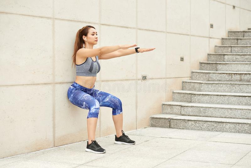 Wall squat. Vietnamese strong young woman doing wall squat royalty free stock photo