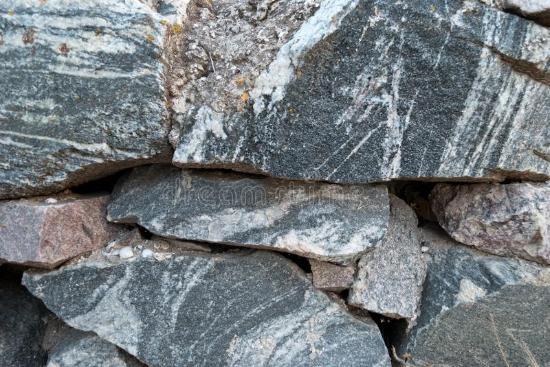 Wall of stones, stone wall texture of gray color on a summer day. Large wall of natural granite stones of different size and color, gray texture on a summer day stock photos