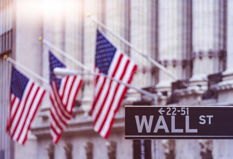 Wall Street American Flags. Wall Street sign with american flags in the Background on a sunny day, Manhattan financial district royalty free stock photo
