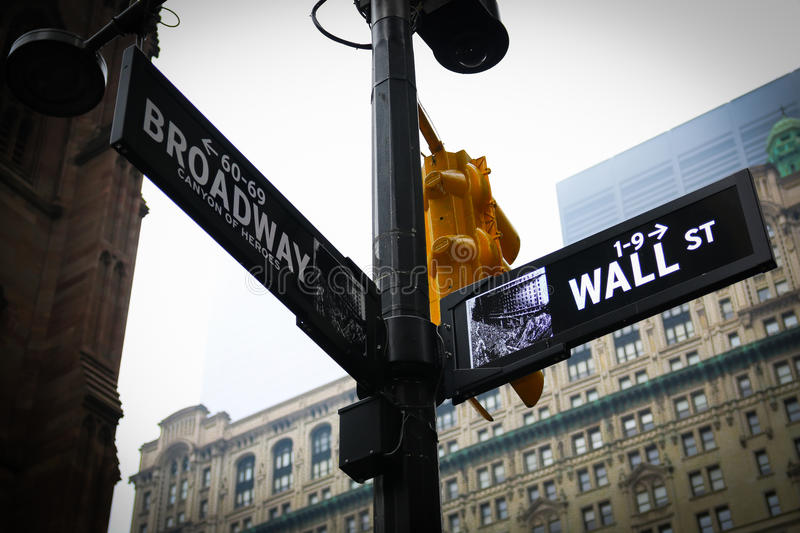Wall Street and Broadway Street Sign New York. Wall Street and Broadway Street Sign in New York with yellow traffic light stock photography