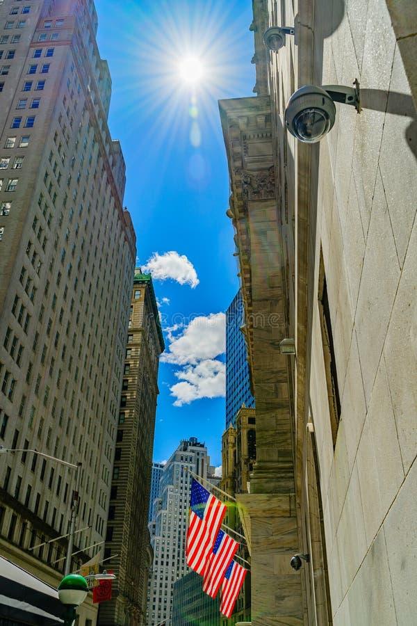 Wall Street, el sol en el cielo ilumina las 3 banderas americanas atadas a la fachada de New York Stock Exchange, financiera fotos de archivo