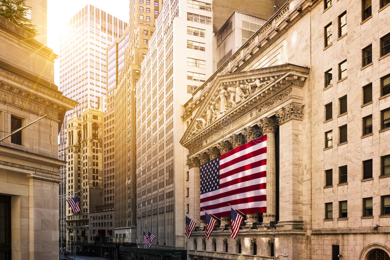 Wall street in New York. Famous Wall street and the building in New York, New York Stock Exchange with patriot flag stock image