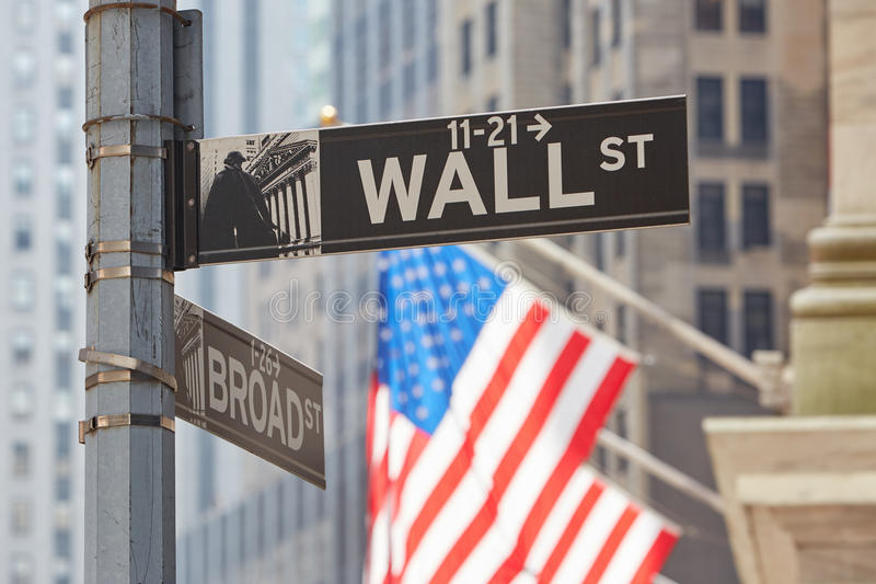 Wall Street sign near Stock Exchange with US flags. Financial district in New York in a sunny day stock photo