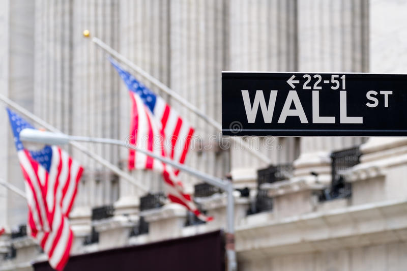 Wall street sign with the New York Stock Exchange on the backgro. Wall street sign with the New York Stock Exchange and american flags on the background royalty free stock photography