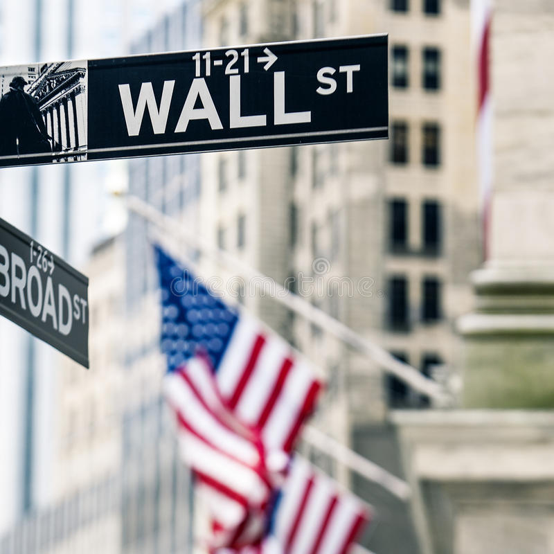 Wall street sign in New York. View of Wall street sign in New York with New York Stock Exchange background royalty free stock photography