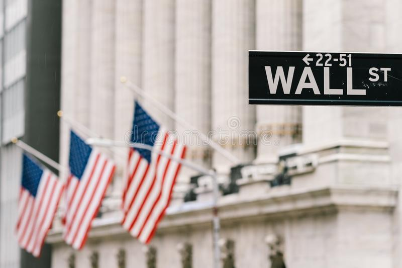 Wall Street sign post with American national flags in background. New York city financial economy district, stock market trade stock photo