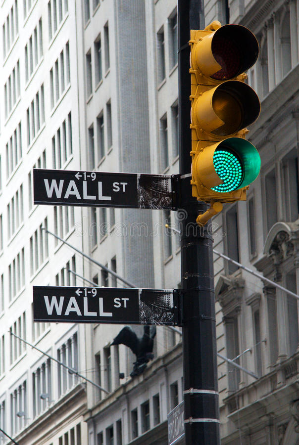 Wall street signs with a green traffic. NEW YORK - JUNE 20: A symbolic photo of Wall street signs with a green traffic light on June 20, 2011 in New York royalty free stock images