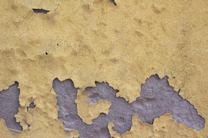 Yellow wall color peeling off because of water, grey plaster showing stock images