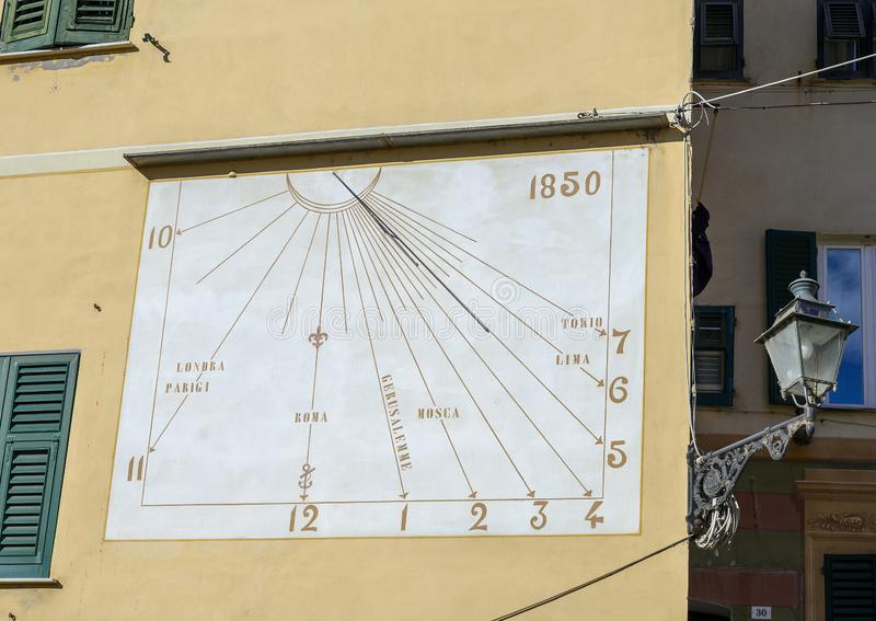 1850 wall sundial in Camogli, Italy, with baroque street lamp. Pictured is a sundial from 1850 on a wall in Camogli, Italy.  To the right is seen a black royalty free stock photo