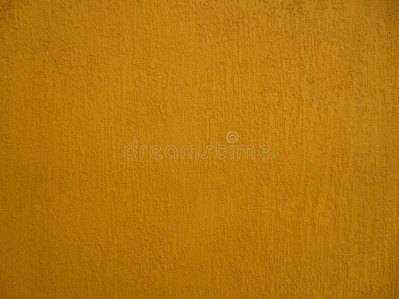 Wall with textured rich dark yellow color. royalty free stock image