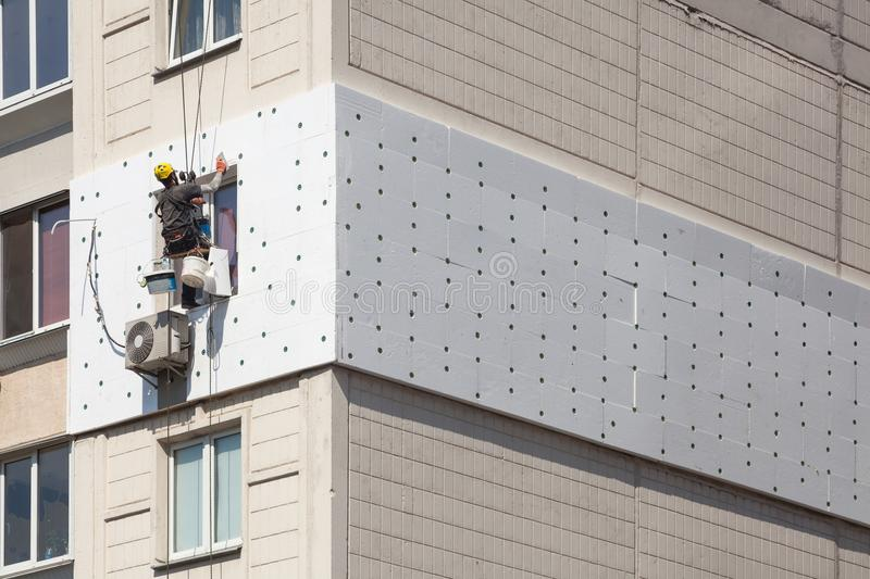 Wall Thermal insulation, industrial climbing, high-altitude work, insulation of walls with foam plastic or Styrofoam. royalty free stock images