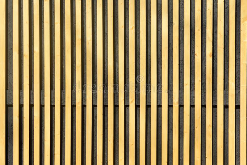 Wall of thin wooden slats. Vertical parallel plates. royalty free stock images