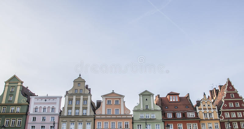 A wall of traditional townhouses in Wroclaw, Poland. A wall of traditional townhouses in Wroclaw, Poland; photographed looking up against a blue sky royalty free stock photography