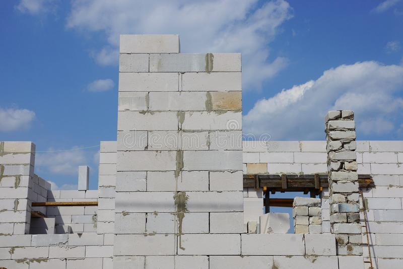Wall of an unfinished house of white bricks. Against the sky and clouds royalty free stock photography