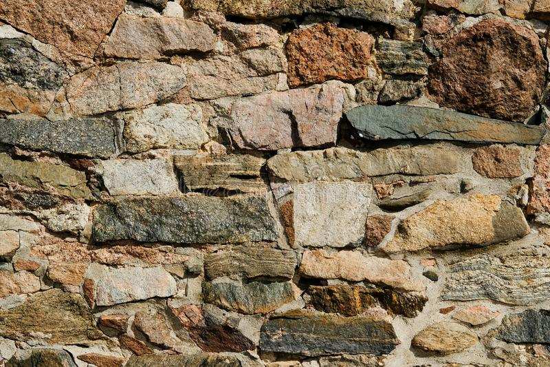 Wall of various stones close-up of different colors and shades of background and testures. Olad wall of various stones close-up of different colors and shades of royalty free stock photo