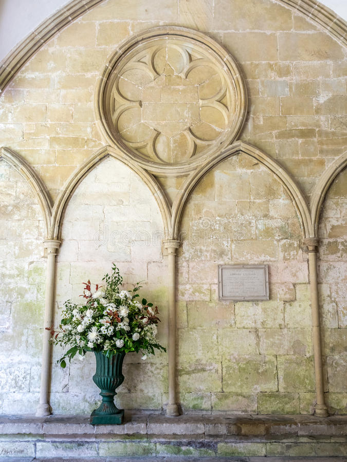 Wall with vest in Salisbury cathedral. Architecture brick wall with gothic art with vest and flower in Salisbury cathedral cloister, England royalty free stock image