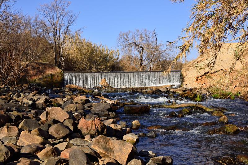 Wall of Water. Water falling over weir in river on farm near Skeerpoort South Africa looking up stream stock photo