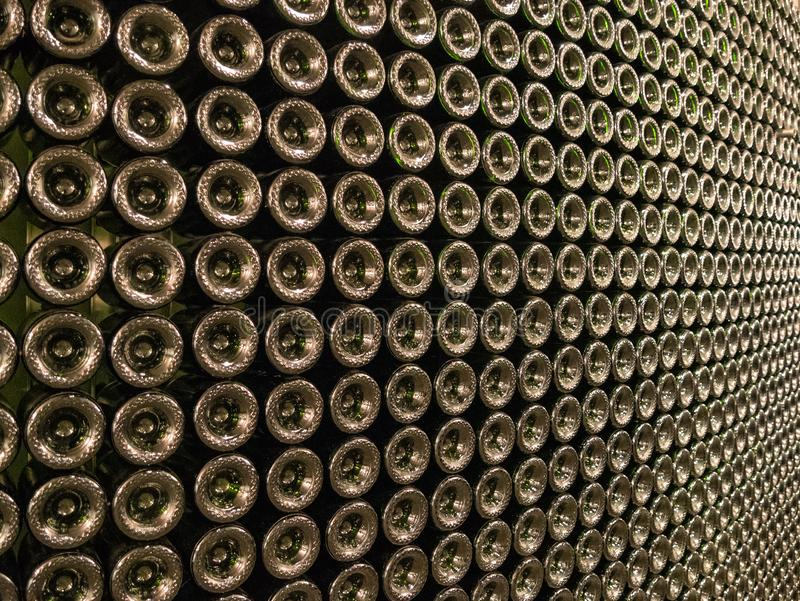 A wall of wine bottles. Pattern on a wall, hundreds of wine bottles, winery artwork royalty free stock photo