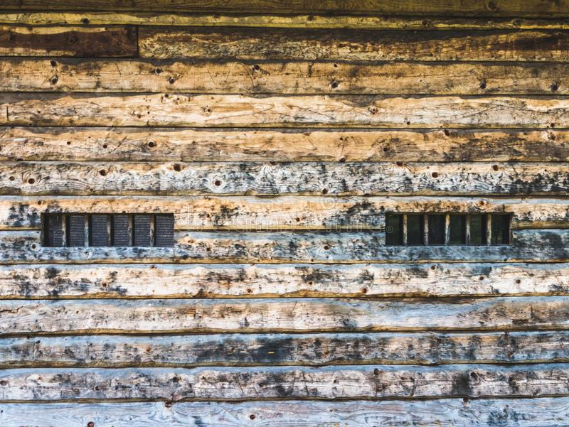 Wall of a wooden barn with windows. On the countryside stock photo